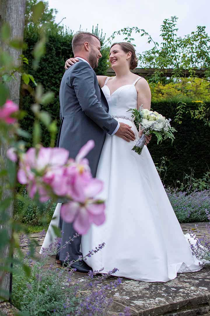 bride and groom standing in a rose garden