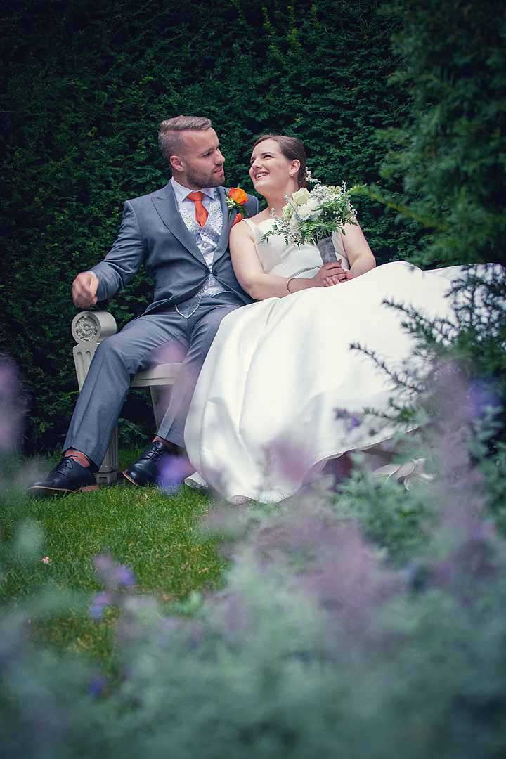 bride and groom sitting in a garden at dusk