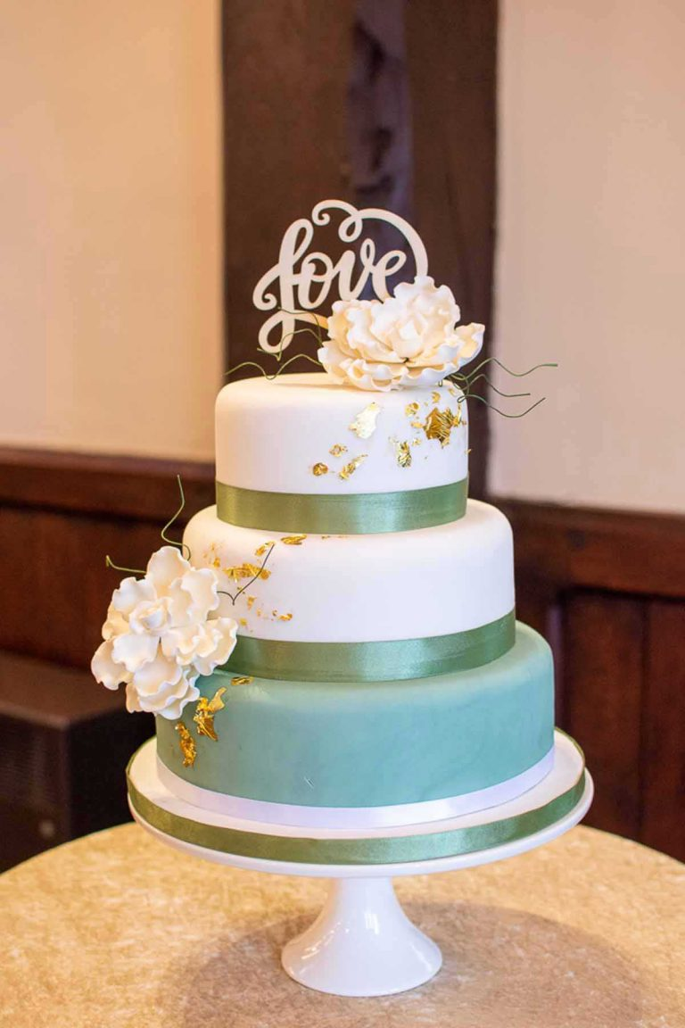three tier wedding cake with white, green and gold decoration