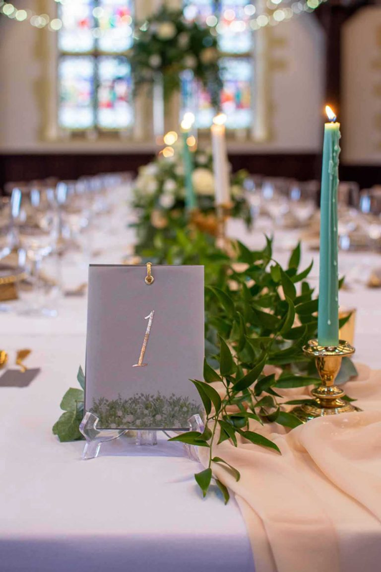 gold foil table name with candles and green foliage
