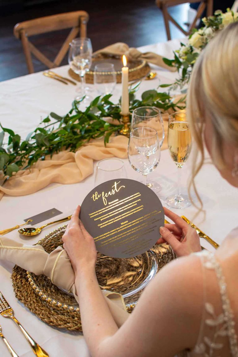 bride holding a gold foil lettered menu