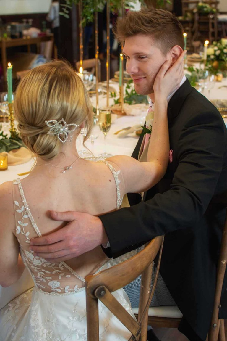 bride touching groom's cheek while seated