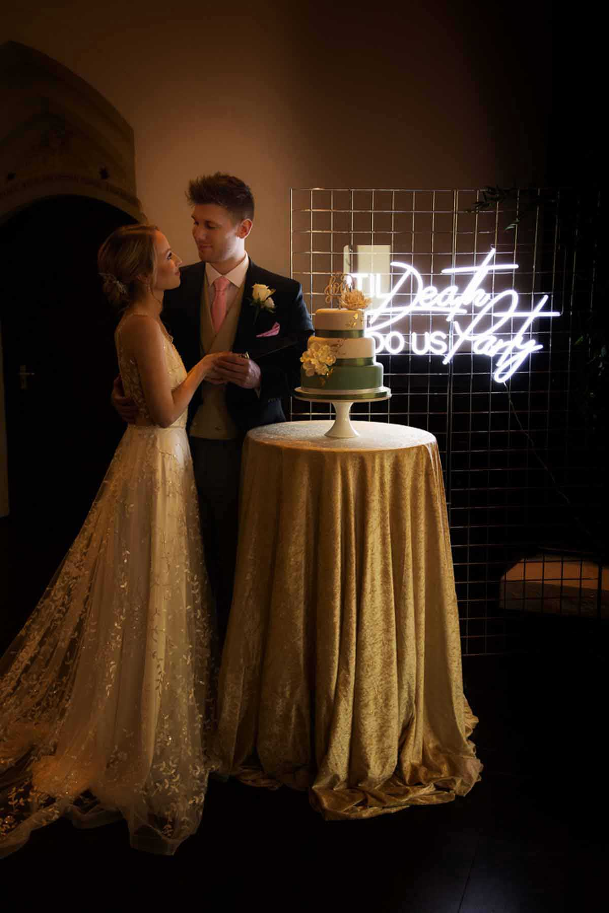 bride and groom about to cut the cake next to a neon sign