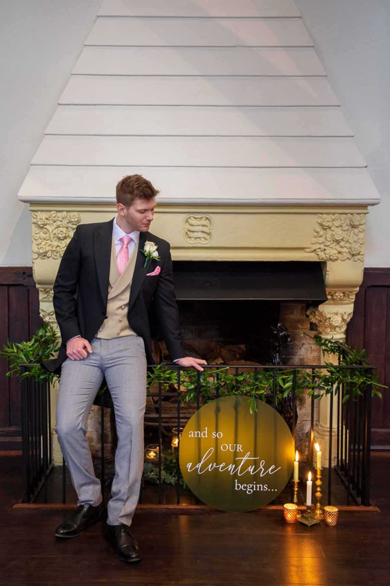 groom standing next to a fireplace