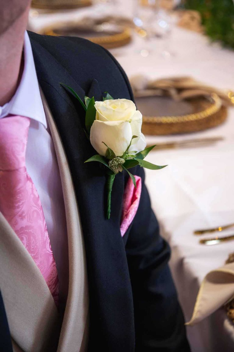 white rose buttonhole on a black suit with pink tie and handkerchief