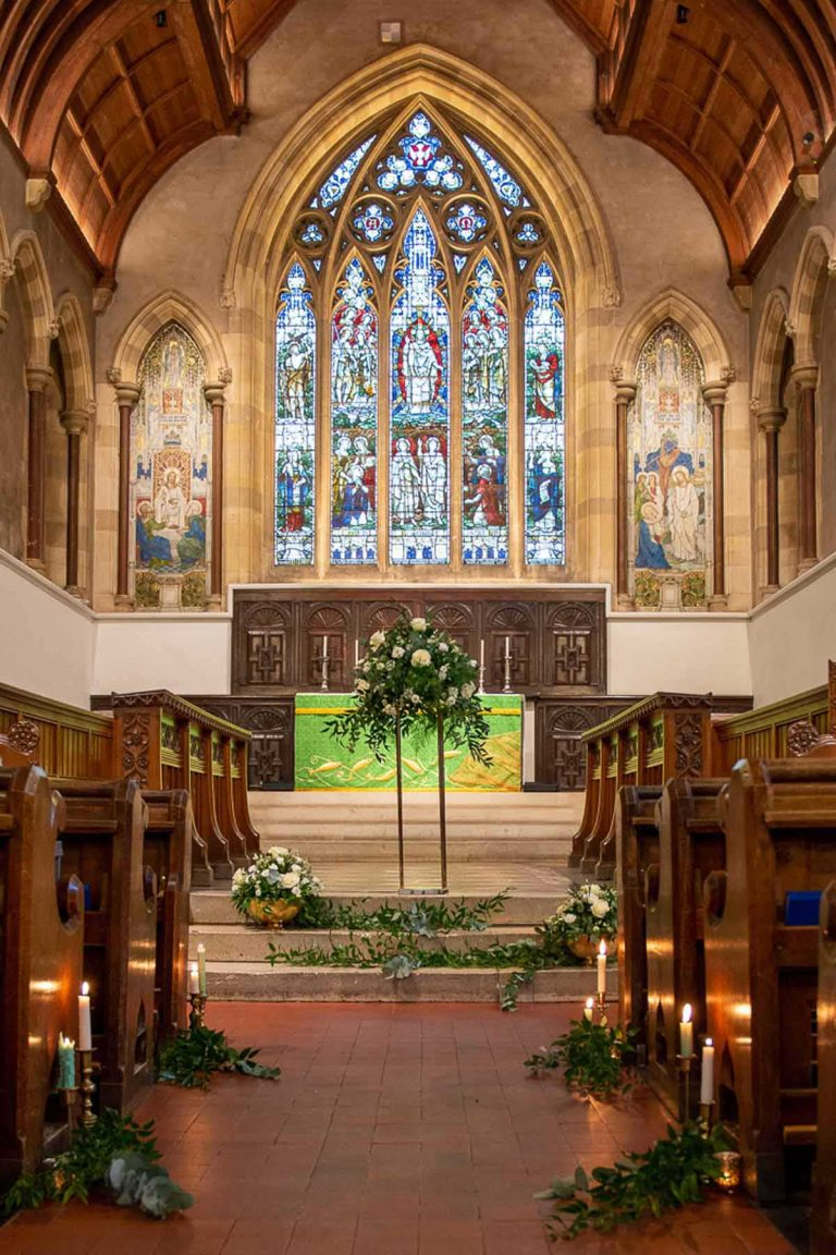 flower arrangements in Bradfield College with large stained glass window