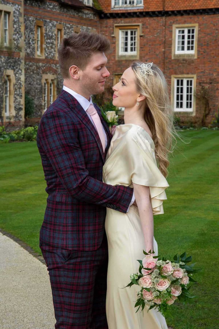 bride in cream dress and groom in plaid suit outside Bradfield College