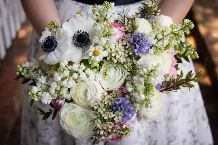 asymmetrical spring wedding bouquet with white pink and blue flowers
