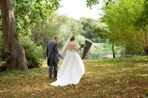 bride and groom walking under autumn trees to a lake