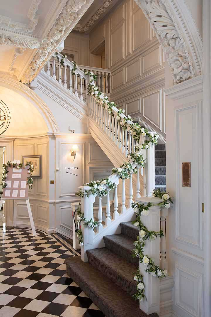 The stairway covered in white rose garlands