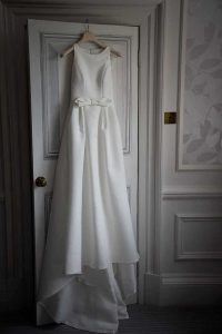 wedding dress with a bow hanging on the back of a door