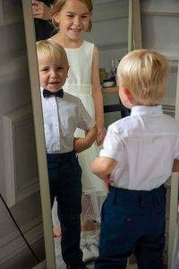 paige boy looking at his reflection in the mirror while flower girl watches