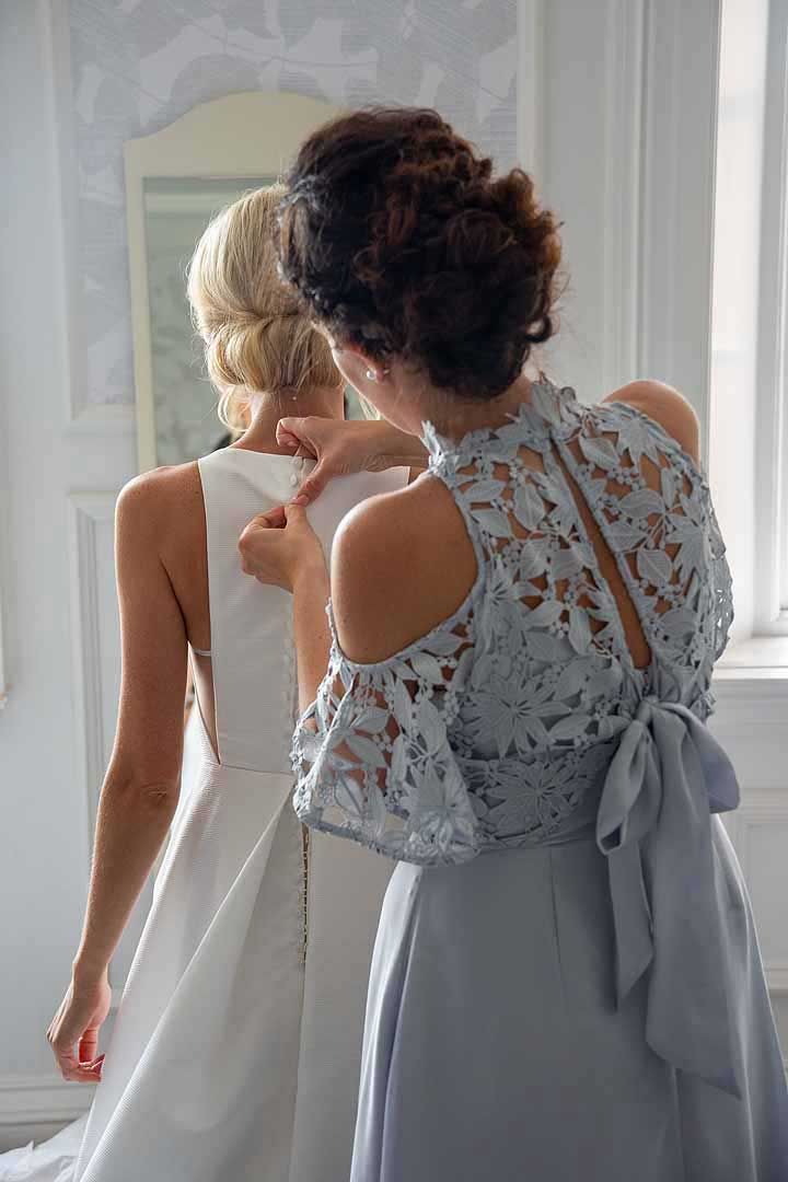 bride having her dress buttons done up by bridesmaid