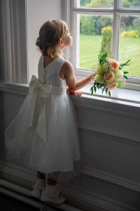 flower girl with bouquet looking out of a window at the garden