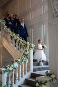 flower girl and grooms party walking down the stairs