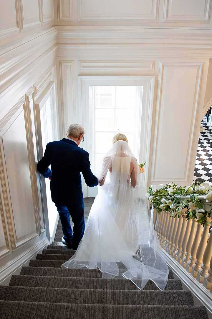 father and bride walking down the stairs