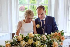 bride and groom signing the wedding register seated behind a garland of white and peach flowers