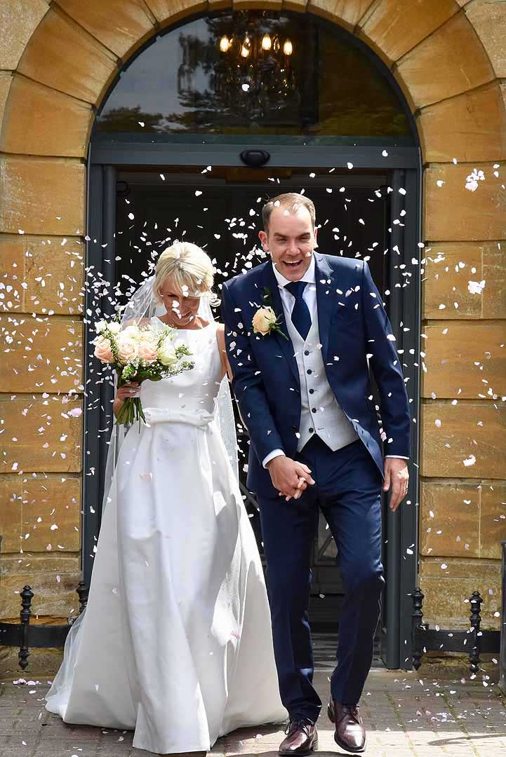 bride and groom being showered by confetti at the door