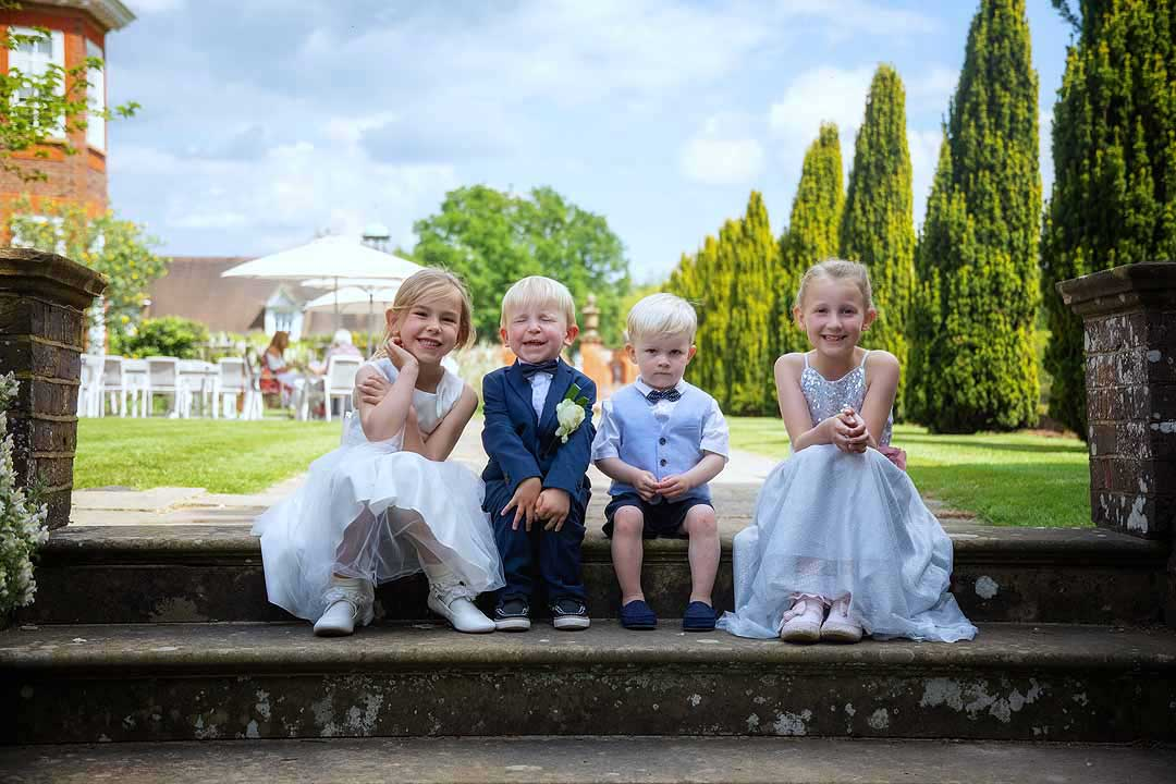 two flower girls and two paige boys sitting on garden steps