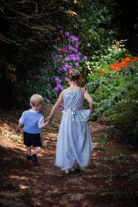 flower girl and paige boy walking down a garden path with flowers