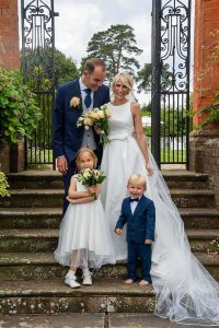 bride and groom on steps with flower girl and paige boy