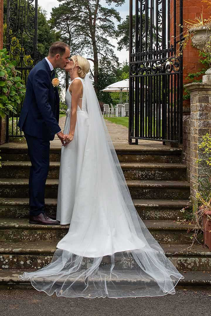 bride and groom having their first kiss on garden steps