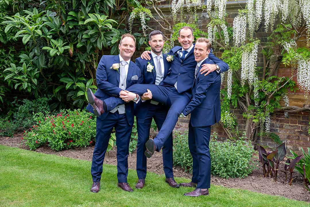 groom being lifted up by his three best men