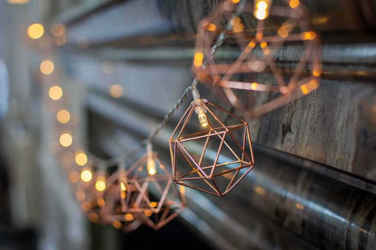 copper geometric fairy lights on a grey marble mantlepiece