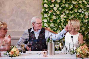 father stroking the brides cheek
