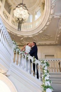 bride and groom standing on the stairs kissing