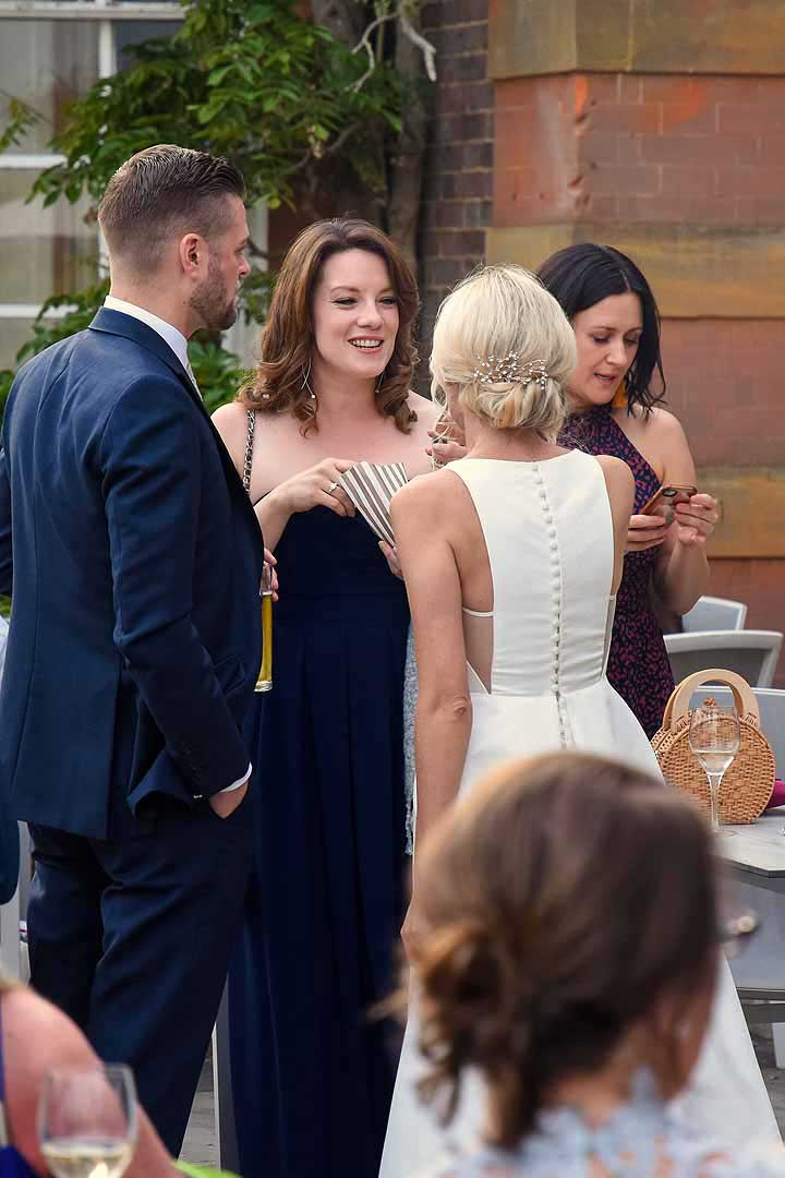 bride chatting with three wedding guests outside