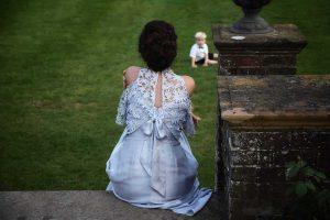 bridemaid sitting on a garden step watching a small boy play on the grass