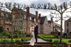 bride and groom standing on step in front of Bradfield College Berkshire