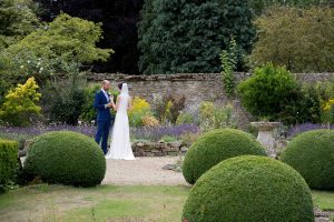 Bride and groom toasting in Caswell House gardens