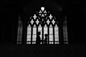 bride and groom silhouetted in church window