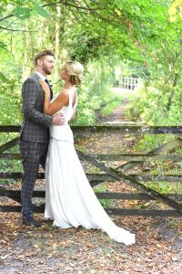bride and groom next to a wooden gate under trees