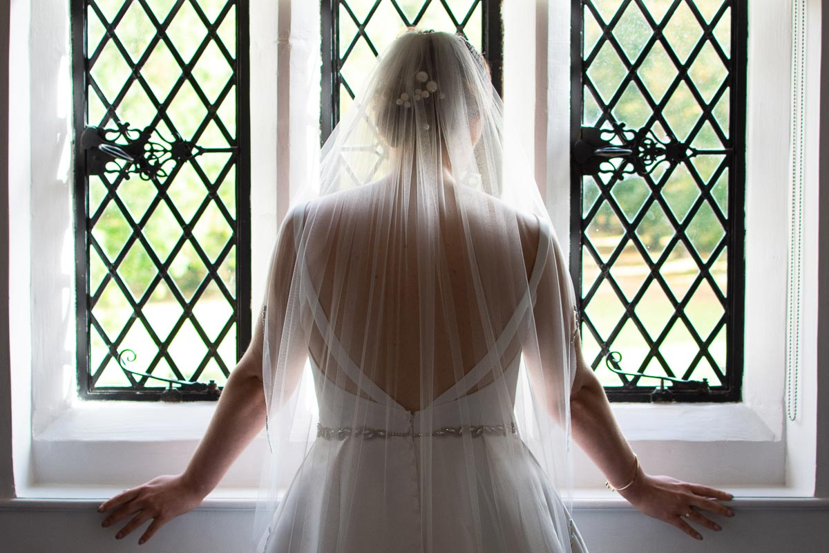 bride with veil looking out of window