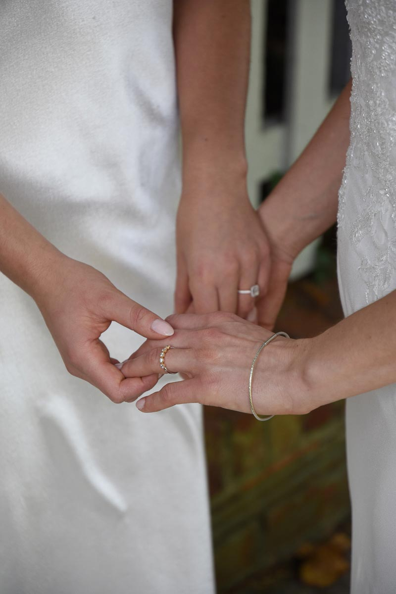 brides holding hands with engagement rings