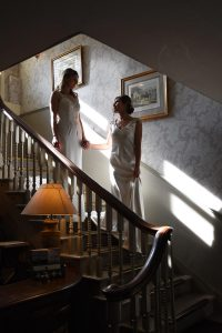 brides looking at each other as they come down the stairs