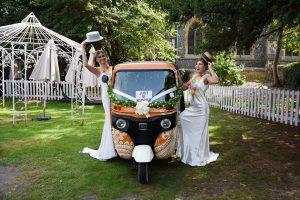 two brides in fancy dress with an orange tuk tuk