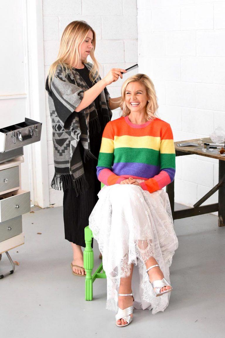 bride wearing rainbow jumper having her hair done