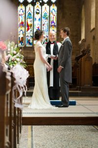 bride groom and vicar in a church