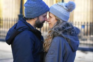 couple in wooly hats nose to nose