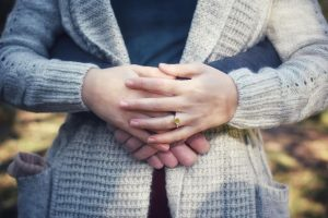 clasped hands and engagement ring
