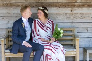 bride in white and red dress with groom sitting on a wooden bench
