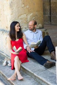 couple sitting on stone steps with books
