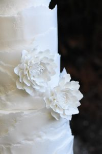 three tiered rough-edged wedding cake with flowers