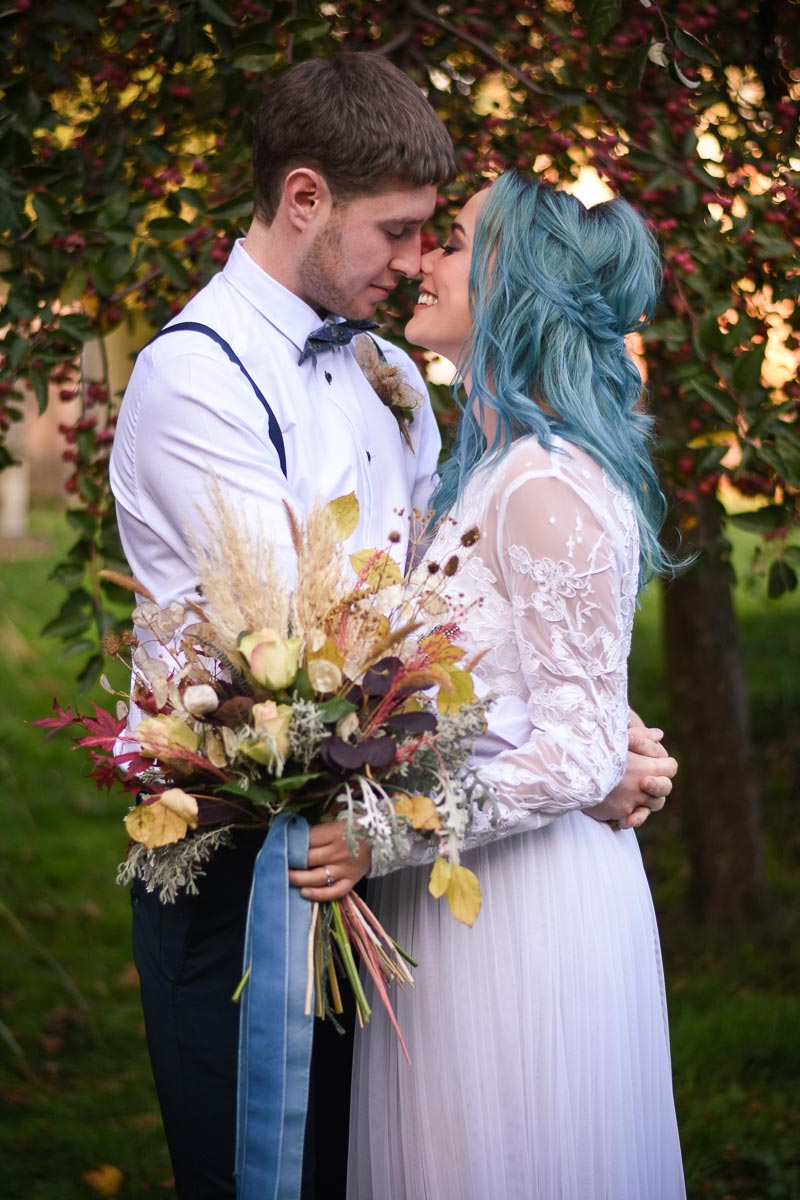 bride with blue hair about to kiss groom
