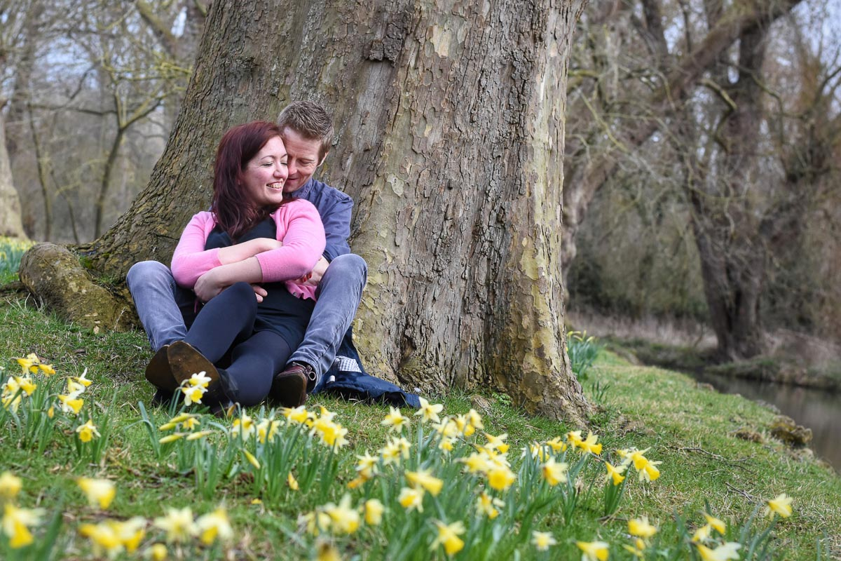 couple sitting with back to tree and daffodils in front of them