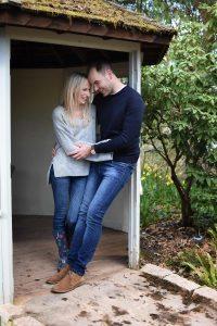 couple standing in a pergola doorway in wisley gardens